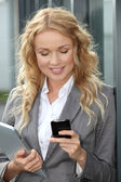 Saleswoman using mobile phone and digital tablet — Foto Stock