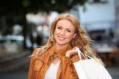 Beautiful woman in town holding shopping bags — Stok fotoğraf