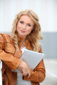 Beautiful woman in town using electronic tablet — Stock Photo