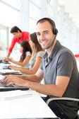 Customer service employee with headphones on — Stock Photo