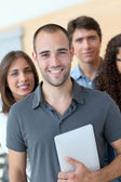 Portrait of student standing with workgroup — Stock Photo