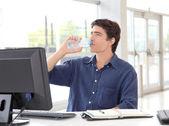 Office worker drinking water in front of desktop computer — Stock Photo