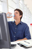 Office worker drinking water in front of desktop computer — Stock Photo