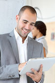 Young businessman using electronic tablet — Stock Photo