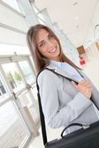 Beautiful young woman standing in hall with briefcase — Stock Photo