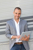 Man leaning on wall with electronic tablet — Stock Photo