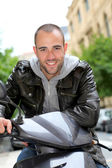 Portrait of young man sitting on motorcycle in town — Stock Photo