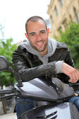 şehir içinde motosiklet üzerinde oturan genç adam portresi — Stok fotoğraf