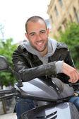 年轻人坐在摩托车在镇上的肖像 — 图库照片