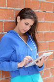 Teenager using electronic tablet in the street — Stock Photo