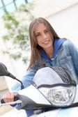 Young woman sitting on motorbike outside — Stock Photo