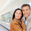 Smiling couple standing outside airport — Stock Photo #18210027
