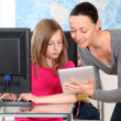 Teacher showing electronic tablet to school girl — Stock Photo