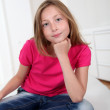 Portrait of blond girl with cross-legged on sofa - Stock Photo