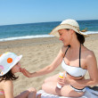 Mother putting sunscreen on her daughter&amp;#039;s face - Foto Stock