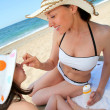 Mother putting sunscreen on her daughter's face — Foto Stock