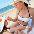 Mother putting sunscreen on her daughter's face — Stockfoto
