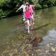 Family crossing river barefoot — Stock Photo #18210597