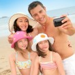 Family taking picture of themselves at the beach — Stock Photo #18210775