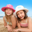 Young girls laying down at the beach — Stock Photo #18210785