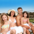 Happy family of 4 sitting at the beach - Stock Photo