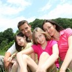 Happy family sitting in park — Stock Photo