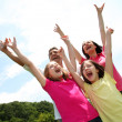 Cheerful family lifting arms up in the air  — Stock Photo