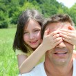 Young girl hiding her father eyes - Stock Photo