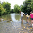 Family crossing river in summer — ストック写真