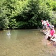 Family playing ricochet in river  — Stockfoto