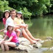 Portrait of family sitting in river in summer — ストック写真