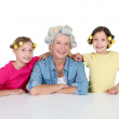 Senior woman and kids with hair curlers — Stock Photo #18210931