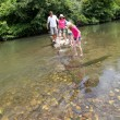 Family crossing river in summer — Stock Photo