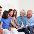 3-generation family sitting in couch with electronic tablet — Stock Photo