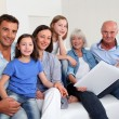 Stock Photo: 3-generation family looking at photo album