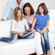 Foto Stock: Parents and children using electronic tablet at home