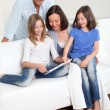 Foto de Stock  : Parents and children using electronic tablet at home