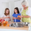 Senior woman making apricot jam with grandkids — Stock fotografie