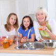 Senior woman making apricot jam with grandkids — Stock Photo