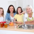Portrait of grandmother, mother and kids in kitchen — Stock Photo