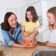 Mother and daughters in kitchen — Stock Photo