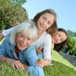 Senior woman lying down in park with girls on his back — Stock Photo