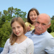 Stock Photo: Grandfather with grandkids sitting in park