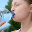 Portrait of young girl drinking water from bottle — Stock Photo #18211475