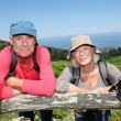 Senior hikers standing by a fence — Stock Photo