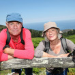 Senior hikers standing by a fence — Stock Photo #18211995