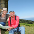 Senior couple looking at map on hiking day - Stockfoto
