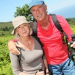 Portrait of happy senior couple hiking in natural landscape — Stock Photo