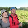 Portrait of happy senior couple hiking in natural landscape - Stock Photo