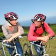 Senior couple riding mountain bikes in natural landscape — Stockfoto